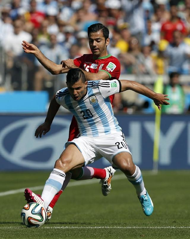 Argentina's Sergio Aguero tries the shield the ball from Iran's Pejman Montazeri during the group F World Cup soccer match between Argentina and Iran at the Mineirao Stadium in Belo Horizonte, Brazil, Saturday, June 21, 2014. (AP Photo/Jon Super)