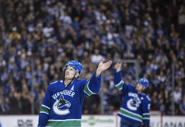 Vancouver Canucks' Daniel Sedin, left, and his twin brother, Henrik Sedin wave to the crowd after the Canucks defeated the Arizona Coyotes 4-3 in the Sedins' final home NHL hockey game, Thursday, April 5, 2018, in Vancouver, British Columbia. (Darryl Dyck//The Canadian Press via AP)