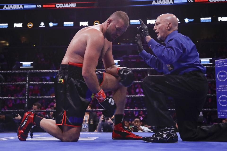 Romania's Razvan Cojanu, left, reacts as the referee counts for him after he was knocked down during the eighth round of a heavyweight boxing match against Nigeria's Efe Ajagba Saturday, March 7, 2020, in New York. Ajagba stopped Cojanu in the ninth round. (AP Photo/Frank Franklin II)