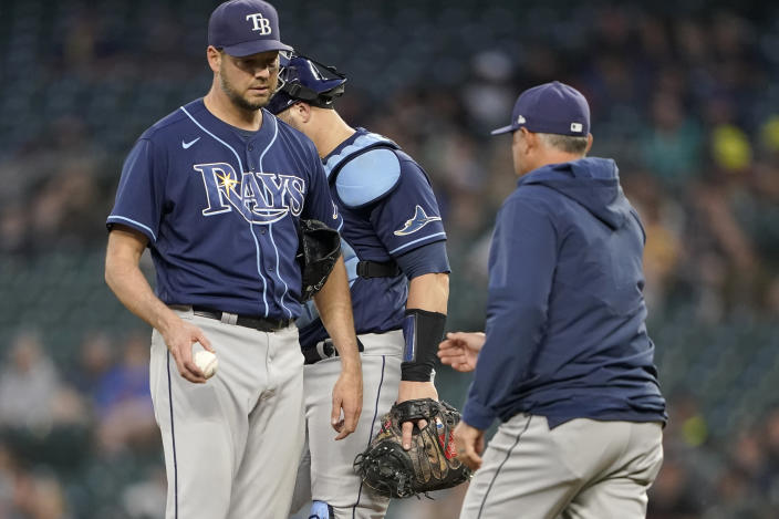 Tampa Bay Rays starting pitcher Rich Hill, left, is pulled from the baseball game against the Seattle Mariners by manager Kevin Cash, right, during the sixth inning Thursday, June 17, 2021, in Seattle. (AP Photo/Ted S. Warren)