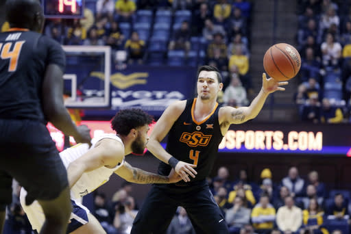 Oklahoma State guard Thomas Dziagwa (4) passes while defended by West Virginia guard Jermaine Haley (10) during the first half of an NCAA college basketball game Saturday, Jan. 12, 2019, in Morgantown, W.Va. (AP Photo/Raymond Thompson)