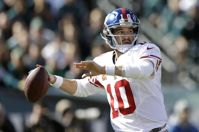 New York Giants quarterback Eli Manning (10) throws a pass against the Philadelphia Eagles during the first half of an NFL football game Sunday, Oct. 27, 2013, in Philadelphia. (AP Photo/Matt Rourke)