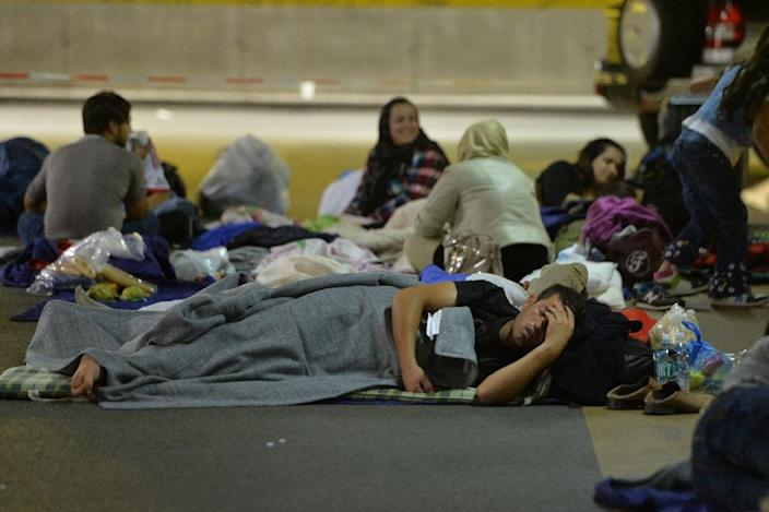 Refugees rest in a car park at the main rail station in Salzburg, Austria, on September 13, 2015 (AFP Photo/Wildbild)