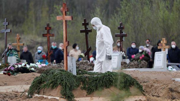 PHOTO: A worker using personal protective equipment walks near a grave while burying a person in a special purpose section of a graveyard on the outskirts of Saint Petersburg, Russia, May 13, 2020. (Anton Vaganov/Reuters)