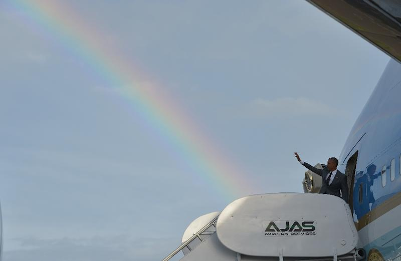 US President Barack Obama makes his way to board Air Force One under a rainbow in Kingston, Jamaica on April 9, 2015 (AFP Photo/Mandel Ngan)
