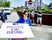 """A woman holds up a sign reading """"justice for Bosnia"""" outside the court in The Hague"""