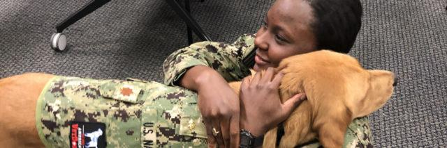 Brelahn Wyatt, a second-year medical student, hugs Shetland, a half-golden retriever, half-Labrador retriever who also happens to be a lieutenant commander in the Navy and a clinical instructor in the Department of Medical and Clinical Psychology at the Uniformed Services University of the Health Sciences. (Julie Rovner/KHN)