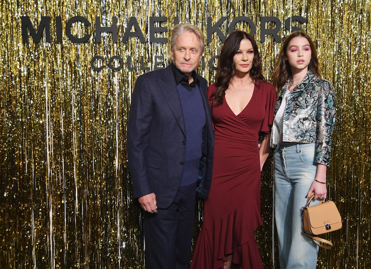 NEW YORK, NY - FEBRUARY 13:  (L-R) Michael Douglas, Catherine Zeta-Jones, and Carys Zeta Douglas attend the Michael Kors Collection Fall 2019 Runway Show at Cipriani Wall Street on February 13, 2019 in New York City.  (Photo by Nicholas Hunt/Getty Images for Michael Kors)