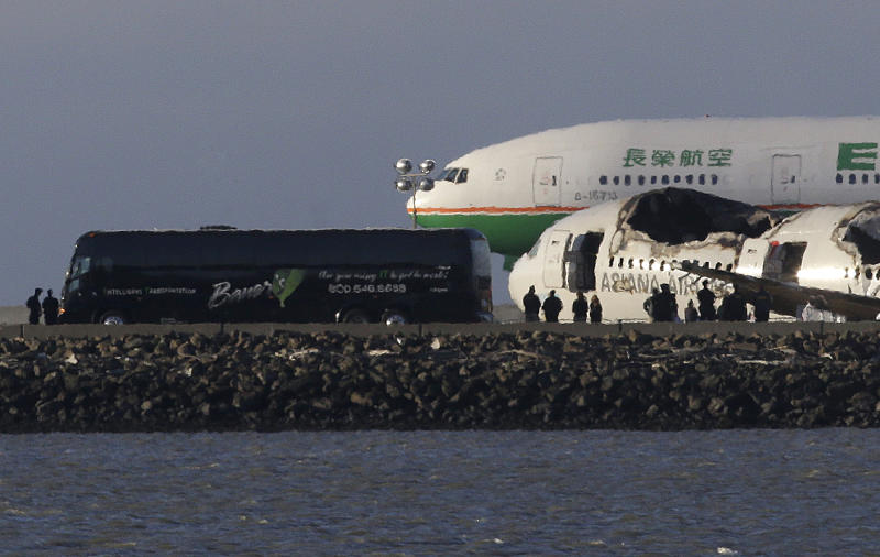A group of people stand in front of the wreckage of Asiana Flight 214, which crashed on Saturday, July 6, 2013, as one of three buses that were reported to be carrying passengers and family members are parked next to it on a tarmac at San Francisco International Airport in San Francisco, Wednesday, July 10, 2013. Two passengers were killed and many others were injured in the crash. (AP Photo/Jeff Chiu)