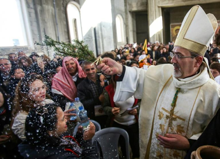 Archbishop Pierbattista Pizzaballa (R) sprinkles holy water from a wet branch on Catholic pilgrims as they attend a mass at the Church of Saint John the Baptist, near the site, where Jesus is believed to have been baptised