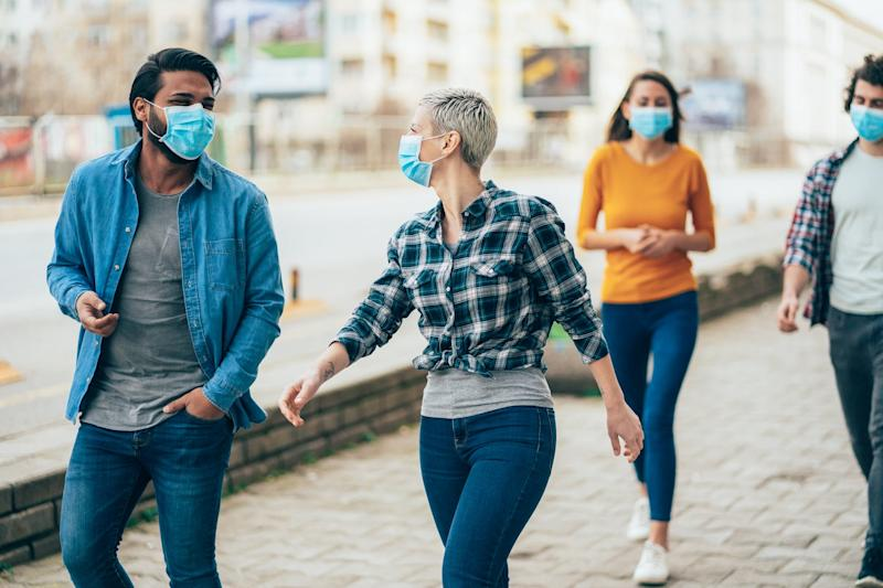 Young people meet in quarantine outside on the city street wearing face protective mask to prevent Coronavirus and anti-smog