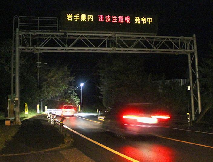 """Cars pass under a tsunami advisory following an earthquake on Route 45 in Kamaishi city, Iwate Prefecture, northeastern Japan, early Saturday, Oct. 26, 2013. The earthquake of magnitude 7.3 struck early Saturday off Japan's east coast, the U.S. Geological Survey said, triggering small tsunamis but causing no apparent damage. Japan's Meteorological Agency said the quake was an aftershock of the magnitude 9.0 earthquake and tsunami that struck the same area in 2011, killing about 19,000 people and devastating the Fukushima Dai-Ichi nuclear power plant. The advisory reads: """"Inside Iwate prefecture tsunami advisory has been issued."""" (AP Photo/Kyodo News) JAPAN OUT, CREDIT MANDATORY"""