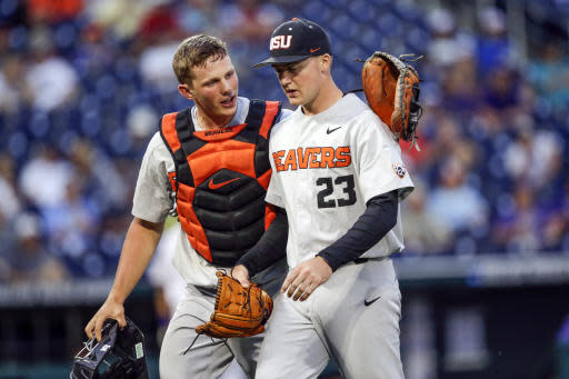 Oregon State pitcher Kevin Abel (23) is congratulated by Oregon State catcher Adley Rutschman after Able stuck out Washington designated hitter Joe Wainhouse to end the seventh inning of an NCAA College World Series baseball elimination game in Omaha, Neb., Monday, June 18, 2018. Oregon State won 14-5. (AP Photo/Nati Harnik)