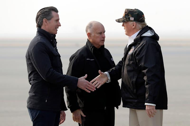 President Donald Trump greets California then-Gov.-elect, and current governor, Gavin Newsom as he arrives on Air Force One at Beale Air Force Base for a visit to areas impacted by the wildfires last November at Beale Air Force Base, Calif., as Gov. Jerry Brown, stands at center. Trump and Newsom have often been at odds politically, often on Twitter.