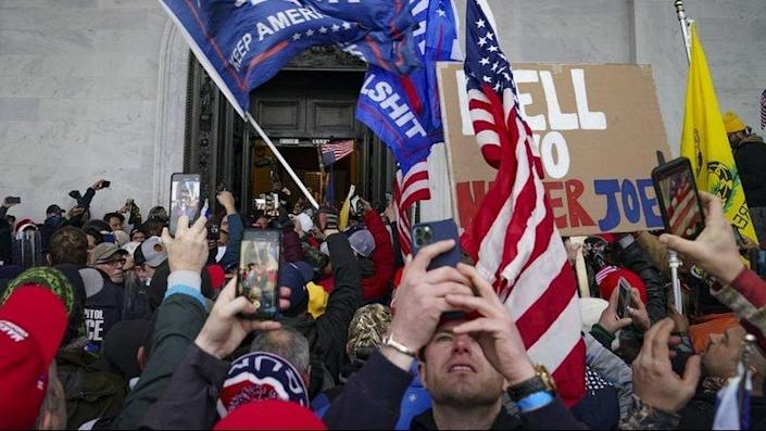 In this Jan. 6, 2021 file photo, Trump supporters gather outside the U.S. Capitol in Washington. Six Capitol Police officers are being disciplined for their actions that day, including posing for photos with participating rioters. (AP Photo/John Minchillo, File)