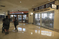 Vistors walk past closed shops inside the Daniel K. Inouye International Airport Thursday, Oct. 15, 2020, in Honolulu. The COVID-19 pandemic has caused a devastating downturn on Hawaii's tourism-based economy. Many stores and restaurants inside the airport remain close due the the economic crisis. (AP Photo/Marco Garcia)