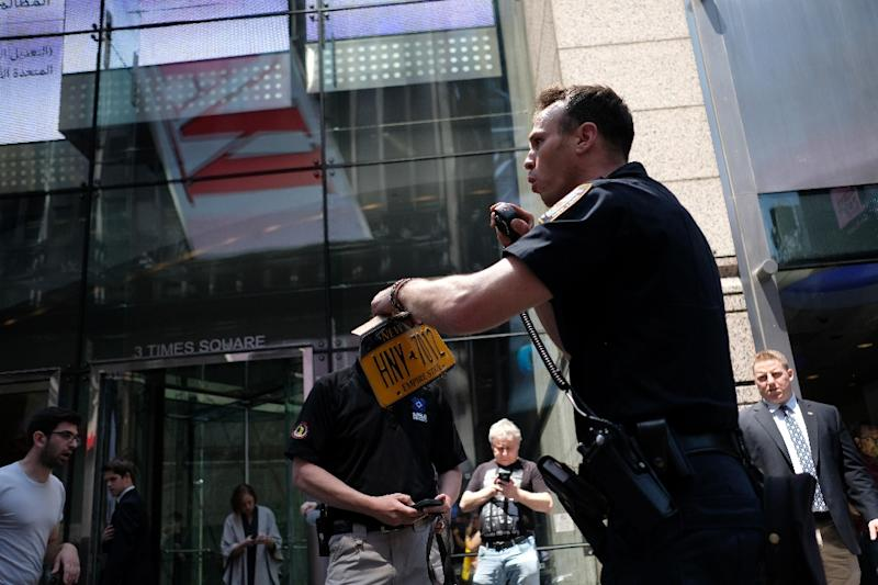 A Police officer collects the license plate of a car after it plunged into pedestrians in Times Square in New York on May 18, 2017 (AFP Photo/Jewel SAMAD)