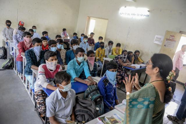Students wearing facemasks or scarves to protect the face attend a class at a governement-run high school in Secunderabad.