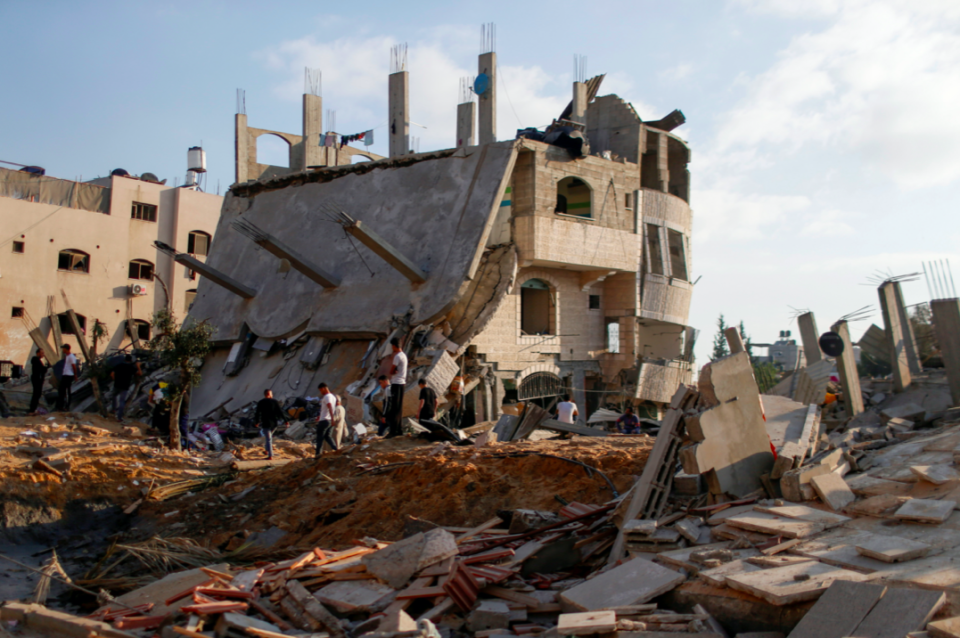 Palestinians gather around the ruins of buildings which were destroyed in Israeli air strikes amid a flare-up of Israeli-Palestinian violence, in the northern Gaza Strip. (Reuters/Mohammed Salem)