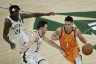 Phoenix Suns guard Devin Booker (1) drives past Milwaukee Bucks guard Pat Connaughton (24) and guard Jrue Holiday (21) during the first half of Game 4 of basketball's NBA Finals Wednesday, July 14, 2021, in Milwaukee. (AP Photo/Aaron Gash)