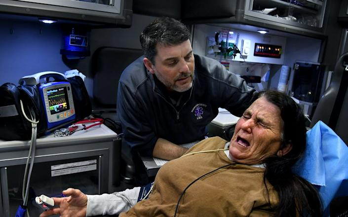 An EMT comforts and helps a woman injured in a car crash.