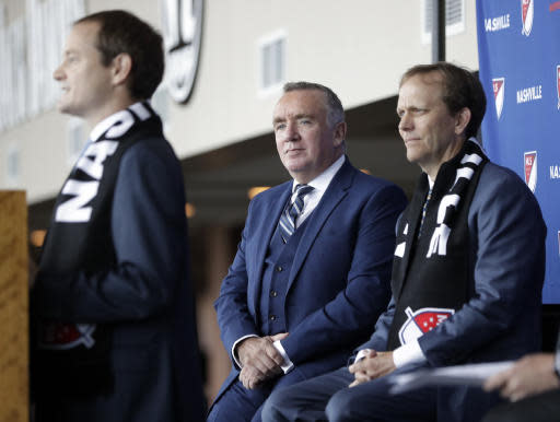 Ian Ayre, center, listens as he is introduced as the first chief executive officer of the Nashville MLS franchise Monday, May 21, 2018, in Nashville, Tenn. Ayre is a former CEO of Liverpool Football Club of the English Premier League. At left is emcee Will Alexander, and at right is franchise lead owner John Ingram. (AP Photo/Mark Humphrey)