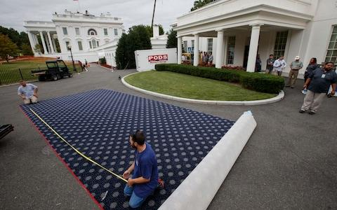 Workmen prepare new carpeting for the West Wing of the White House in Washington, Friday, Aug. 11, 2017, as it undergoes renovations while President Donald Trump is spending time at his golf resort in New Jersey - Credit: AP