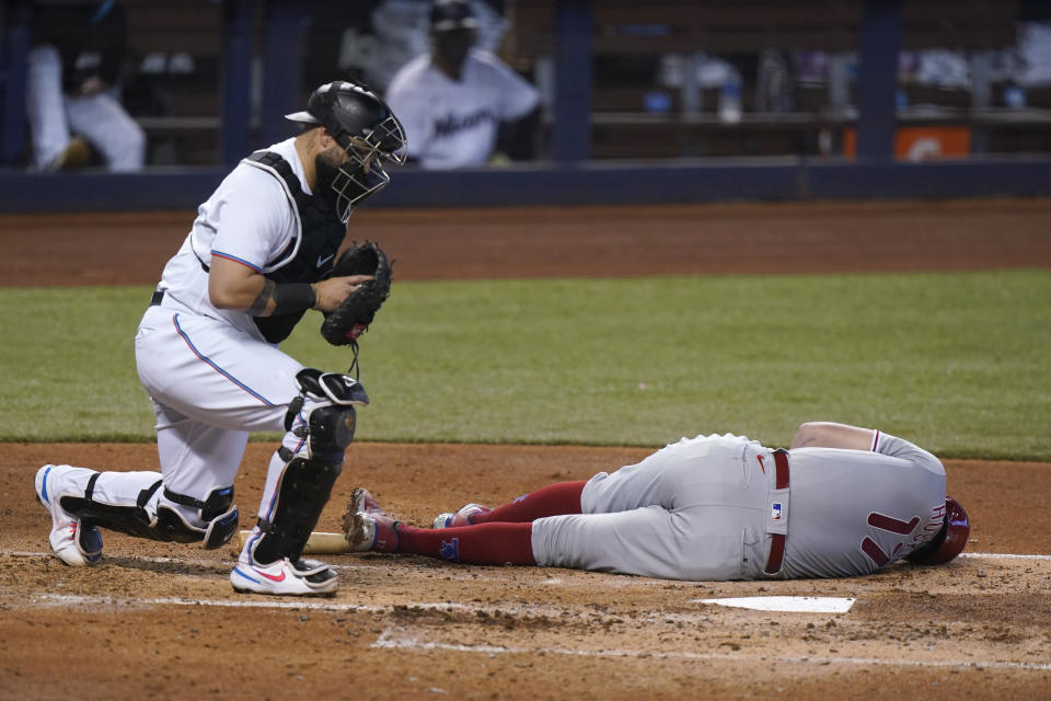 Miami Marlins catcher Sandy Leon, left, checks on Philadelphia Phillies' Rhys Hoskins after Hoskins dove to the ground on a close pitch during the fourth inning of a baseball game, Thursday, May 27, 2021, in Miami. (AP Photo/Wilfredo Lee)