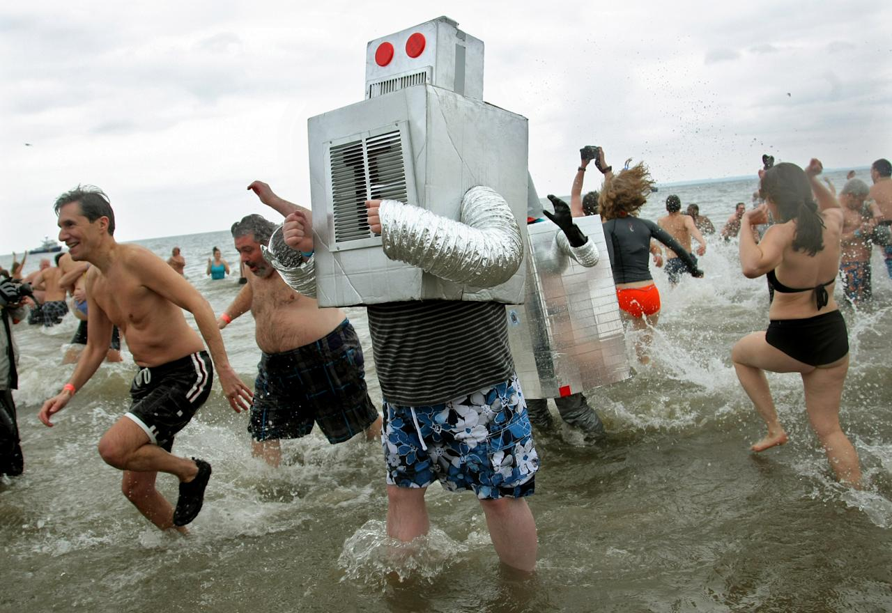 NEW YORK, NY - JANUARY 1:  People wearing costumes take part in the Coney Island Polar Bear Club's New Year's Day swim on January 1, 2013 in the Coney Island neighborhood of the Brooklyn borough of New York City. The annual event attracts hundreds who brave the icy Atlantic waters and temperatures in the upper 30's as a way to celebrate the first day of the new year. (Photo by Monika Graff/Getty Images)