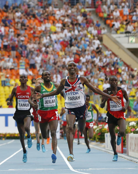 Britain's Mo Farah, center, reacts as he crosses the finish line to win the men's 10,000-meter final at the World Athletics Championships in the Luzhniki stadium in Moscow, Russia, Saturday, Aug. 10, 2013. (AP Photo/Anja Niedringhaus)