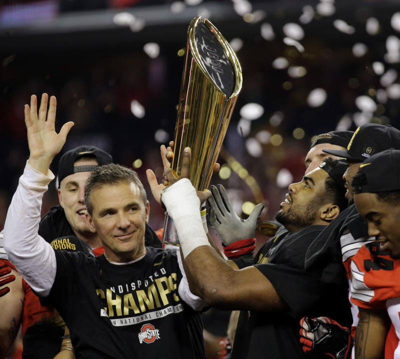 FILE - This Jan. 12, 2015, file photo shows Ohio State head coach Urban Meyer and Ezekiel Elliott celebrating after the NCAA college football playoff championship game against Oregon in Arlington, Texas. The Ohio State Buckeyes won their first College Football Playoff national championship. (AP Photo/Eric Gay, File)
