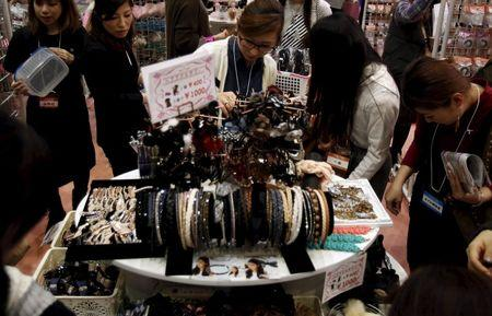 A woman looks at hair accessories displayed at an exhibition and sale during Tokyo Nail Expo 2015 in Tokyo