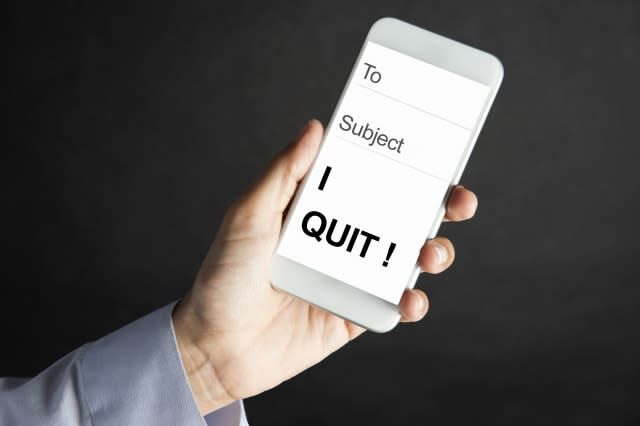 Female hand is showing e-mail on smart phone with 'I quit' message to camera.