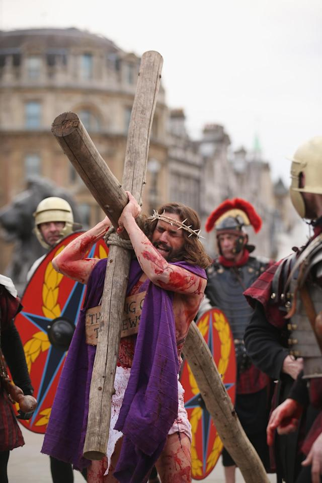 LONDON, ENGLAND - MARCH 29: Actor James Burke-Dunsmore (C) plays Jesus in 'The Passion of Jesus' on Good Friday to crowds in Trafalgar Square on March 29, 2013 in London, England. The Wintershall Players are based on the Wintershall Estate in Surrey and perform several biblical theatrical productions per year. Their production of 'The Passion of Jesus' includes a cast of 78 actors, horses, a donkey and authentic costumes of Roman soldiers in the 12th Legion of the Roman Army. (Photo by Oli Scarff/Getty Images)