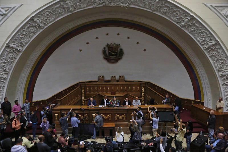 Lawmakers Luis Parra, center, Franklyn Duarte, right of Parra, and Jose Noriega, left of Parra, give a press at the National Assembly in Caracas, Venezuela, Monday, Jan. 6, 2020. The previous day, lawmakers loyal to President Nicolas Maduro rushed to choose Parra as their new legislative president, while many opposition lawmakers were blocked from entering the voting session. The other two men are unidentified. (AP Photo/Andrea Hernandez Briceño)
