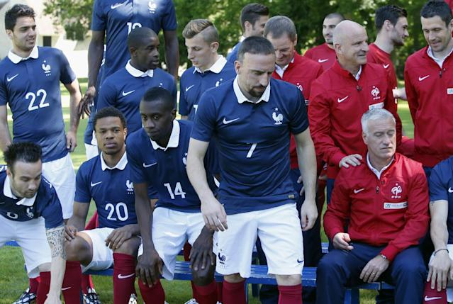 France's forward Franck Ribery, foreground walks, as France's assistant coach Guy Stephan, right holds the shoulder of head coach Didier Deschamps, right bottom, after the posing for the French National soccer team photo, at the training base, in Clairefontaine, outside Paris, Friday, June 6, 2014. France's World Cup ambitions were dealt a significant blow when winger Franck Ribery failed to overcome a back injury and was ruled out of the squad on Friday. Coach Didier Deschamps hoped Ribery would play a part in the friendly against Jamaica on Sunday, but the Bayern Munich winger was replaced by Montpellier winger Remy Cabella. (AP Photo/Francois Mori)