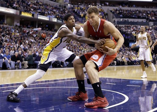 Indiana Pacers forward Paul George, left, reaches around Los Angeles Clippers forward Blake Griffin for the ball in the first half of an NBA basketball game in Indianapolis, Thursday, Feb. 28, 2013. (AP Photo/Michael Conroy)