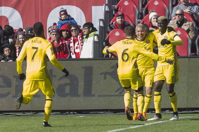 Columbus Crew's Gyasi Zerdes (11) celebrates with Cristian Martinez and Will Trapp (6) after scoring his team's second goal against Toronto FC during the second half of an MLS soccer game in Toronto, Saturday, March 3, 2018. (Chris Young/The Canadian Press via AP)