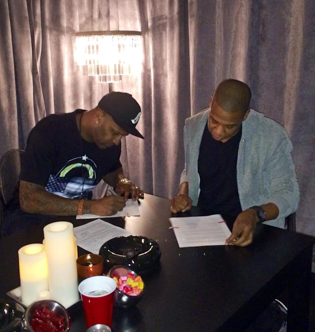 In this photo provided by Roc Nation Sports, New York Yankees pitcher CC Sabathia, left, signs papers with Jay-Z as Sabathia signs on with Jay-Z's sports agency, Roc Nation Sports, Thursday, Jan. 16, 2014, in New York. Sabathia will join former teammate Robinson Cano in Roc Nation Sport's emerging client base. (AP Photo/Roc Nation Sports)