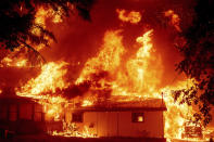 Flames consume a home as the Dixie Fire tears through the Indian Falls community in Plumas County, Calif., Saturday, July 24, 2021. The fire destroyed multiple residences in the area. (AP Photo/Noah Berger)