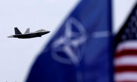 FILE PHOTO: NATO and U.S. flags flutter as U.S. Air Force F-22 Raptor fighter flies over the military air base in Siauliai