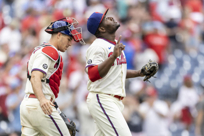 Philadelphia Phillies closing pitcher Hector Neris, right, gestures as he walks with catcher J.T. Realmuto after the Phillies defeated the Miami Marlins in a baseball game, Sunday, July 18, 2021, in Philadelphia. (AP Photo/Laurence Kesterson)