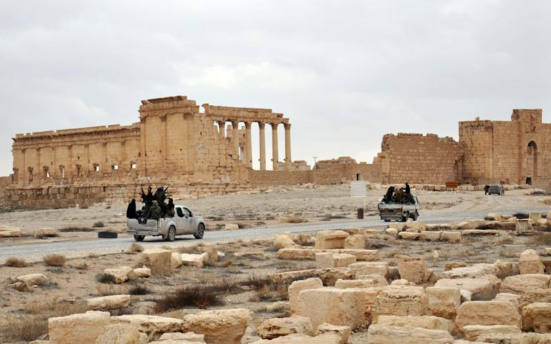 Syrian troops drive up to the ancient ruins in Palmyra, after recapturing the town on Thursday - Credit: AFP