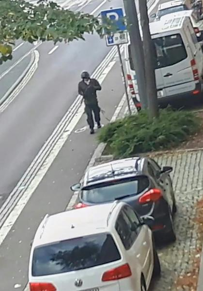 In this screenshot taken from a video by ATV-Studio Halle, a man walks with a gun in the streets of Halle an der Saale in eastern Germany at the time of a deadly shooting at a synagogue and restaurant