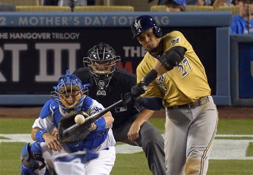 Milwaukee Brewers' Carlos Gomez, right, hits a two-run home run as Los Angeles Dodgers catcher A.J. Ellis, left, watches during the seventh inning of a baseball game, Saturday, April 27, 2013, in Los Angeles. (AP Photo/Mark J. Terrill)