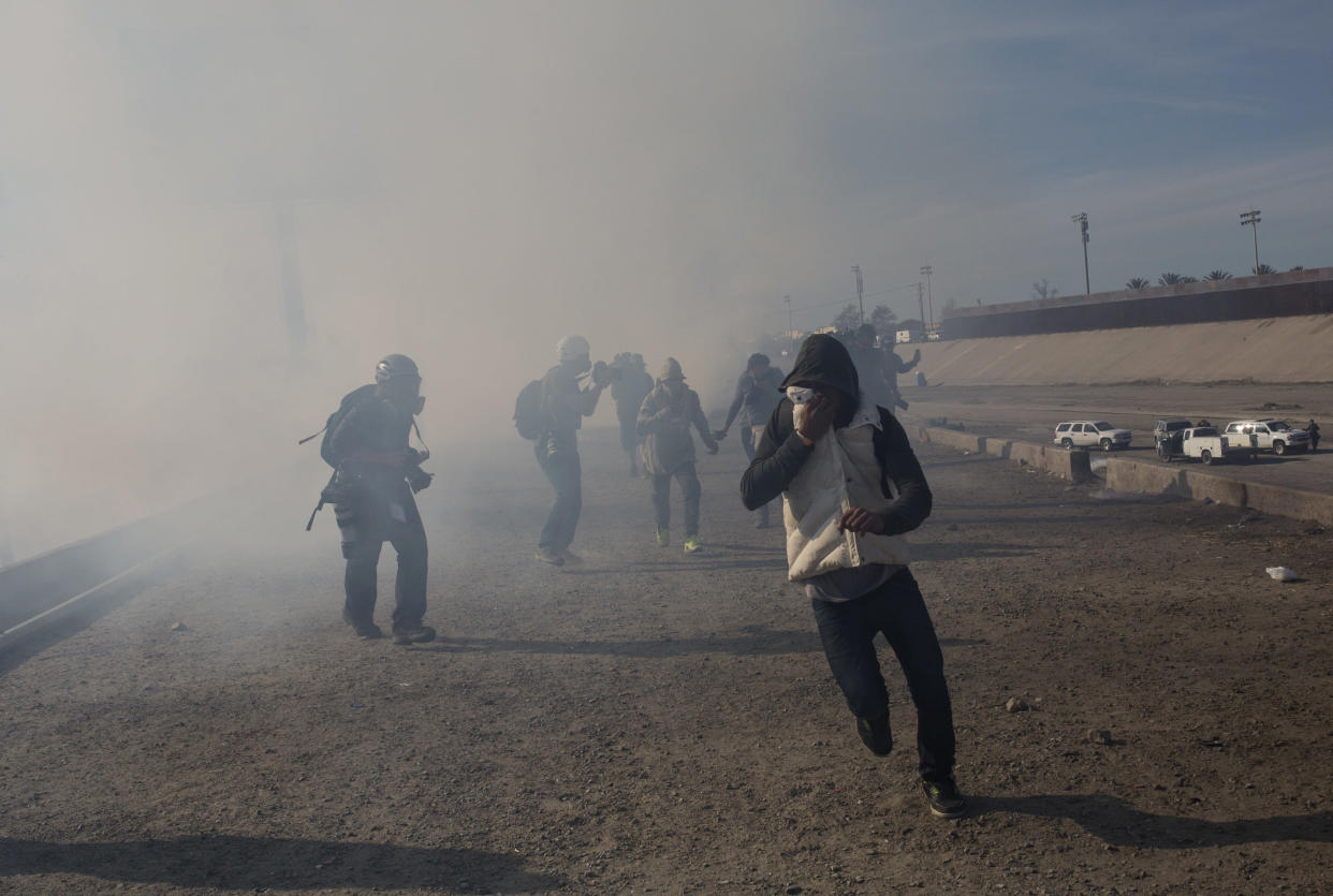 Migrants cover from tear gases launched by US brother patrol agents at the Mexico-U.S. border in Tijuana, Mexico, Sunday, Nov. 25, 2018, as they try to reach the U.S. (Photo: Rodrigo Abd/AP)
