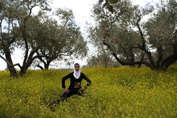 Palestinian runner Worood Maslaha, 20, stretches as she practices with her trainer Saher Jura (unseen) at a field belonging to her family in the West Bank village of Asira Ash-Shamaliya near Nablus, March 27, 2012.