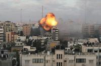 Smoke and flames are seen following an Israeli air strike on a building, amid a flare-up of Israeli-Palestinian fighting, in Gaza City