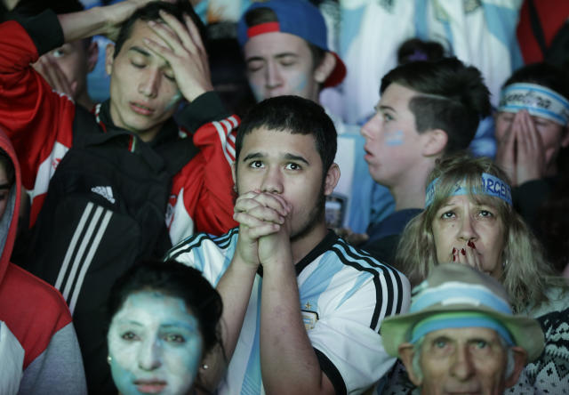 Argentina soccer fans watch in disbelief the final World Cup match between Argentina and Germany on an outdoor television screen set up in Buenos Aires, Argentina, Sunday, July 13, 2014. Mario Goetze volleyed in the winning goal in extra time to give Germany its fourth World Cup title with a 1-0 victory over Argentina. (AP Photo/Jorge Saenz)