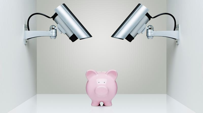 A piggy bank in a small room monitored by two CCTV cameras.
